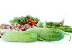 Nya gurkor med grönsaken i bakgrund Arkivbild
