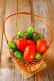 Nya gurkor och tomater i en korg på en gammal trätabell Royaltyfri Fotografi