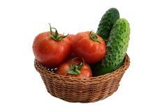 Nya gurkor och tomater i en vide- korg Arkivbild