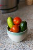 Nya gurkor och tomater i ett exponeringsglas på tabellen Arkivfoto