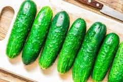 Nya gurkor på skärbrädan i dropparna av vatten Royaltyfria Foton