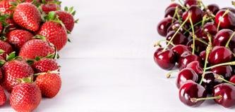 Nya härliga mogna bär på jordgubbar och Cherry Frame Long för en vit träbakgrund söta arkivfoton
