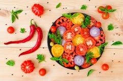 Nya högg av tomater på en platta på en trätabell Fotografering för Bildbyråer