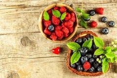 Nya hallon och blåbär på en gammal trätabell Fruktplockning sund frukt Försäljningar av blåbär och hallon royaltyfria bilder