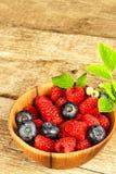 Nya hallon och blåbär på en gammal trätabell Fruktplockning sund frukt Försäljningar av blåbär och hallon arkivbilder