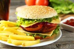 Nya hamburgare på plattan på en grå träbakgrund Fotografering för Bildbyråer