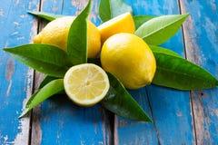 Nya hela och klippta halva citroner önskar sidor på trägammal blå bakgrund Royaltyfri Bild