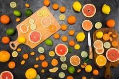 Nya hela och skivade citrusfrukter på skärbrädor på svart Royaltyfri Foto