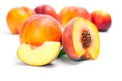 Nya hela persikor med snittet som isoleras på vit bakgrund Arkivbilder