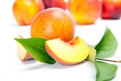 Nya hela persikor med snittet som isoleras på vit bakgrund Arkivfoton