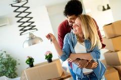 Nya hem för ung lycklig parinflyttning och uppackningsaskar royaltyfri foto