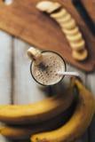 Nya hemlagade banansmoothie och bananer på den vita lantliga trätabellen som är sund Arkivbilder