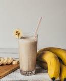 Nya hemlagade banansmoothie, skärbräda och bananer på vitt lantligt trä Arkivfoton