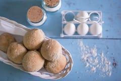 Nya hemlagade bullar på en korg med ägg och kruset av salt Fotografering för Bildbyråer