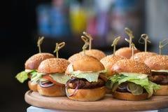 Nya hemlagade hamburgare på träbräde i en restaurang Fotografering för Bildbyråer