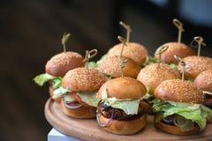 Nya hemlagade hamburgare på träbräde i en restaurang Arkivbild