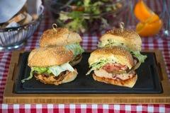 Nya hemlagade hamburgare på träbräde i en restaurang Royaltyfri Foto