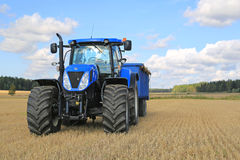 Nya Holland Tractor och jordbruks- släp på fält i höst Royaltyfri Fotografi