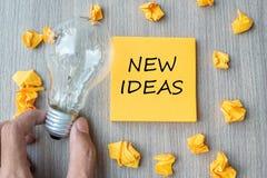 Nya idéord på gul anmärkning och smulat papper med affärsmaninnehavlightbulben på trätabellbakgrund Id?rikt, royaltyfri bild