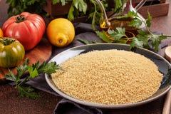 Nya ingredienser för tabboulehsallad: couscous tomater, citron, persilja, mintkaramell, olivolja, spansk peppar Arkivfoton