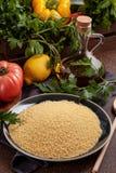 Nya ingredienser för tabboulehsallad: couscous tomater, citron, persilja, mintkaramell, olivolja, spansk peppar Royaltyfri Bild