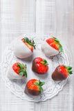 Nya jordgubbar doppade i mörk och vit choklad på ljust bakgrundsslut upp Läcker efterrätt- och godisstång Arkivfoton