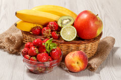 Nya jordgubbar i den glass bunken, nektarin, limefrukt, kiwi, lodisar arkivfoto