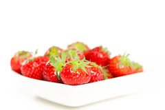 Nya jordgubbar i en bunke som isoleras på white Royaltyfri Bild