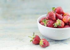 Nya jordgubbar i en keramisk bunke på lantligt trä för turkos Fotografering för Bildbyråer