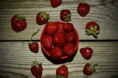 Nya jordgubbar i en kopp på träbakgrund royaltyfri foto