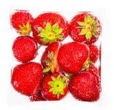 Nya jordgubbar i en kub som isoleras Arkivfoton