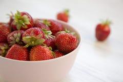 Nya jordgubbar i en rosa keramisk bunke på den vita trätabellen, royaltyfri fotografi