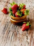 Nya jordgubbar i en träbunke, selektiv fokus Arkivfoton