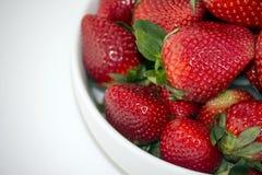 Nya jordgubbar i en vit bunke som isoleras på vit bakgrund Royaltyfri Bild