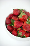 Nya jordgubbar i en vit bunke som isoleras på vit bakgrund Royaltyfri Foto