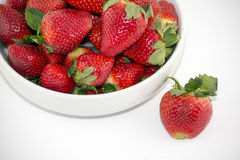 Nya jordgubbar i en vit bunke som isoleras på vit bakgrund Fotografering för Bildbyråer