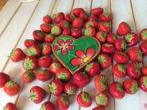 Nya jordgubbar i härd formar korgen med förälskelsemeddelandet Arkivbild