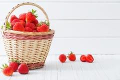 Nya jordgubbar i korg på träbakgrund Fotografering för Bildbyråer