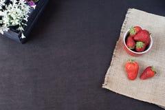 Nya jordgubbar i mini- metall ösregnar på hessiansjute Vit och lilan blommar i en dekorativ träspjällåda Svart bakgrund royaltyfri fotografi