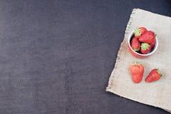 Nya jordgubbar i mini- röd bunke på hessiansjute Svart bakgrund royaltyfria bilder