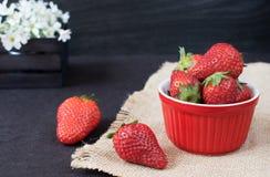 Nya jordgubbar i mini- röd bunke på hessiansjute Vit och lilan blommar i en dekorativ träspjällåda Svart bakgrund arkivfoto