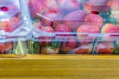 Nya jordgubbar i packe för plast- ask på marknaden Arkivfoto