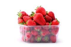 Nya jordgubbar i plast- ask på vit bakgrund Arkivbild