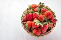 Nya jordgubbar i rottingkorg Arkivfoto