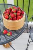 Nya jordgubbar i träkorg på tabellen Royaltyfri Fotografi