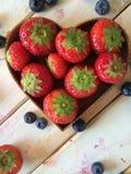 Nya jordgubbar och blåbär i härd formar korgen Arkivbild