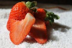 Nya jordgubbar och ett av dem delas och tuggan Fotografering för Bildbyråer