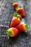 Nya jordgubbar på gammal träbakgrund Arkivfoton