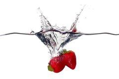Nya jordgubbar plaskar i vatten som isoleras på vit bakgrund Royaltyfri Foto