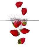 Nya jordgubbar plaskar i vatten som isoleras på vit bakgrund Arkivbild